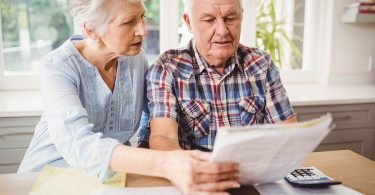 elderly-couple-looks-at-finances