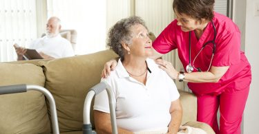elderly-woman-being-assisted-by-nurse