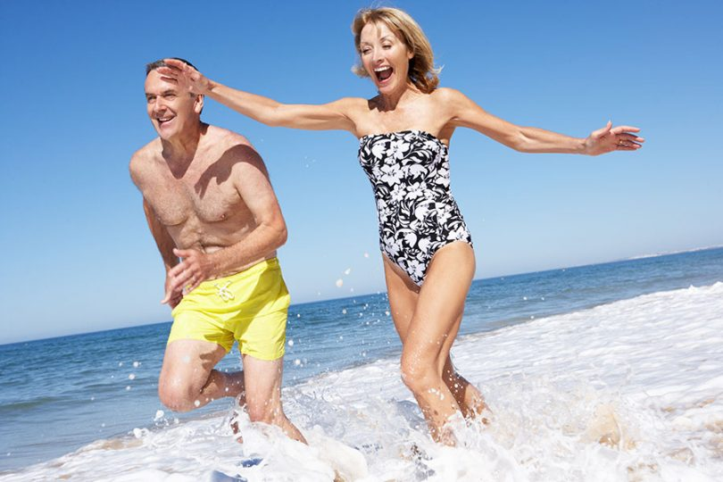 elderly-couple-splash-at-the-beach