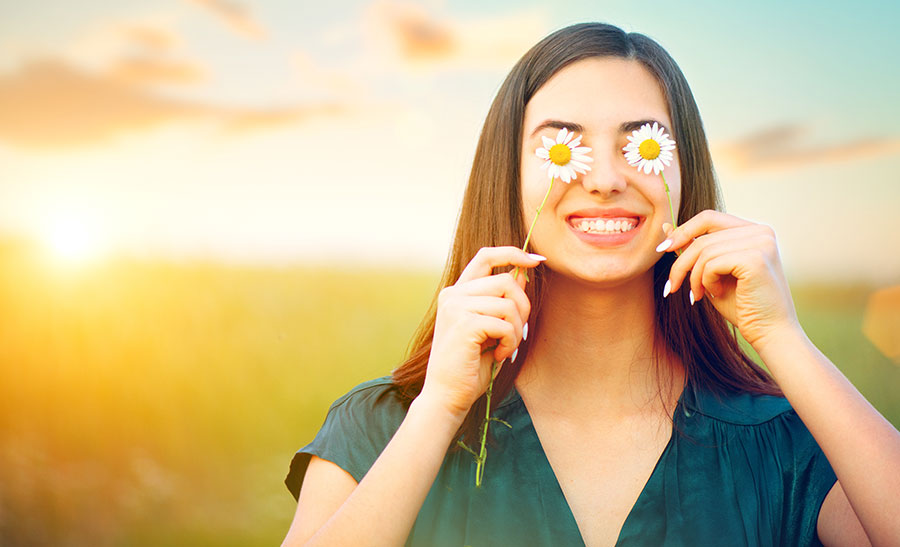 YOUNG-WOMAn-COVERING-HER-EYES-WITH-DAISIES