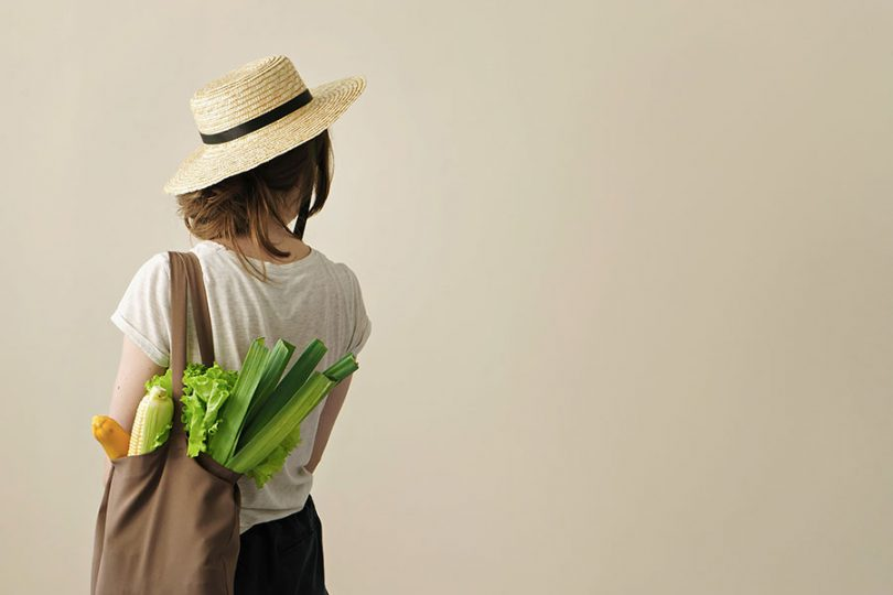 Young-woman-carrying-groceries-in-fabric-bag