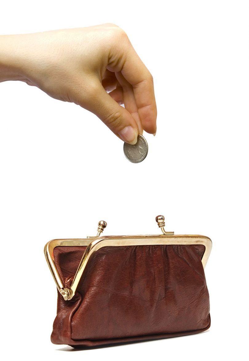 hand-putting-coin-in-brown-leather-coin-purse
