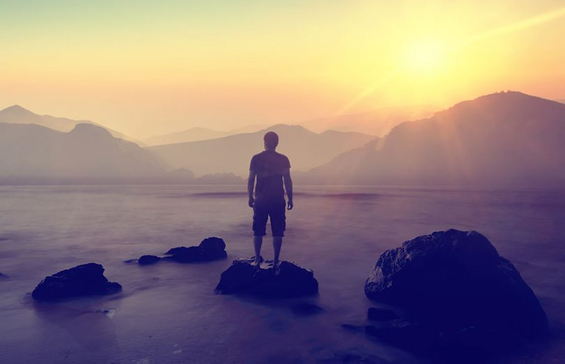 man-watching-sunrise-over-mountains