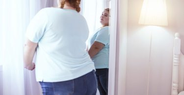 overweight-woman-looking-at-mirror