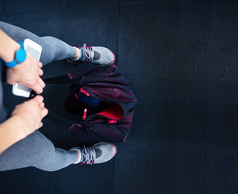woman-holding-cellphone-gym-bag-on-the-floor